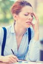 Stressed professional woman sitting outside corporate office closeup portrait young at table having headache out negative Stock Photography