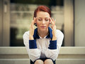 Stressed sad woman sitting outdoors having headache. City urban life style stress Royalty Free Stock Photo
