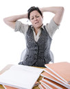 Stressed teacher trying to mark a pile of students work Royalty Free Stock Photography