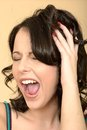 Stressed tense attractive young woman shouting a dslr royalty free image an angry with hand on head with eyes closed looking away Royalty Free Stock Photos
