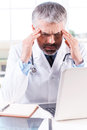 Stressed and tired doctor depressed mature grey hair touching his head with hands while sitting at his working place Stock Photos