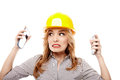 Stressed woman engineer using two cell phone at the same time wearing protection helmet and being overwhelmed by a conversation Stock Image