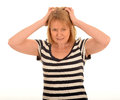 Stressed woman half body portrait of pulling at her hair with a white studio background Royalty Free Stock Images