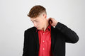 Stressed young business man looking down sad unhappy wearing a black suit and a red shirt Royalty Free Stock Images