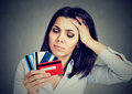 Stressed young woman in debt holding at multiple credit cards