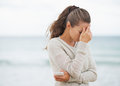Stressed young woman in sweater on beach with cell phone long hair Stock Image