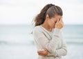Joven mujer en suéter en playa célula