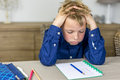 Stressful homework boy struggling with his holding his hands in his hair Stock Images