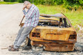 Stressful man on burned down car wreck on the side of the road Royalty Free Stock Photo