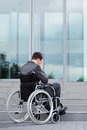 Stressful man on wheelchair before work in business centre Stock Photography