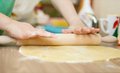 Stretched dough on the kitchen table closeup of woman hands Royalty Free Stock Photo