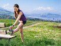 Stretching before jogging photo of a young woman her leg she starts to run on a country path city and lake in the distance Stock Images