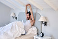 Stretching man waking up exhausted arms early morning after from comfortable bed at home Royalty Free Stock Images