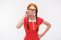 Strict young woman with two braids pointing up Royalty Free Stock Photo
