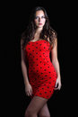 Striking model in dress well proportioned red polka dot on dark background Royalty Free Stock Photo