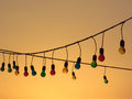 String of Multicoloured Light Bulbs at Sunset Royalty Free Stock Photo