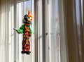 String puppet gazing outside window in sun Royalty Free Stock Photo