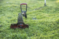 String trimmer lies on mown lawn middle of the yard Royalty Free Stock Photo