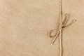 String or twine tied in a bow on kraft paper Royalty Free Stock Photo