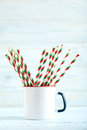 Striped drink straws on a blue wooden background Stock Image
