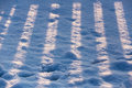 Striped fence shadow on snow Royalty Free Stock Photo