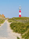Striped lighthouse in a dunes Royalty Free Stock Photo