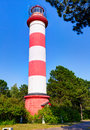 Striped lighthouse in the forest. Royalty Free Stock Photo