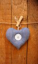 Striped love heart hanging on wooden background Stock Images