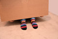 Striped socks looking out under a paper box Royalty Free Stock Photography