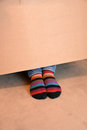 Striped socks looking out under a paper box Stock Images