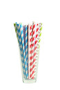 Striped straws for cocktails in glass on white background. Royalty Free Stock Photo