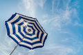 Striped sun umbrella under brightly shining Royalty Free Stock Images