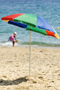 Striped umbrella on a sandy beach Stock Image