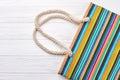 Striped women handbag, wooden background. Royalty Free Stock Photo