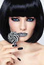 Stripes conceptual portrait of young beautiful blue eyed brunette with striped lips and lollipop in her hand Royalty Free Stock Images