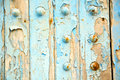 Stripped paint in the yellow nail blue wood door and rusty Stock Photo