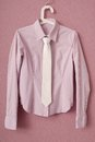 Stripy blouse and tie is on hanger Royalty Free Stock Images
