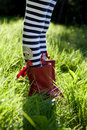 Stripy legs and red boots on grass. Stock Photo