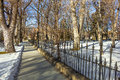 Stroll in winter a walkway along a wrought iron fence invites for a under bare trees Royalty Free Stock Photography