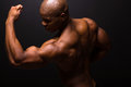 Strong african bodybuilder american posing on black background Stock Image