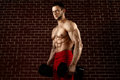 Strong angry Muscular guy posing with dumbbells Royalty Free Stock Photo