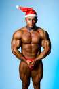 Strong athletic man in a cap of Santa Claus Royalty Free Stock Photography