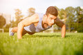 Strong athletic man doing exercises on sports field