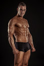 Strong athletic man fitness model torso showing big muscles over black background Stock Photos