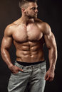 Strong athletic man fitness model torso showing big muscles over black background Royalty Free Stock Images