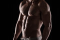 Strong athletic man fitness model torso showing six pack abs isolated on black background Stock Images