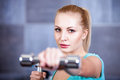 Strong blonde woman weightlifting at the gym doing shoulders exercise caucasian Royalty Free Stock Images