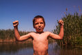 Strong boy flexing muscles outdoors standing in a river Royalty Free Stock Image