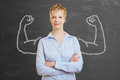 Strong business woman with muscles chalk in front of a blackboard Royalty Free Stock Images