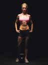 Strong fitness woman with toned muscles portrait of a in sportswear standing on black background Stock Photos